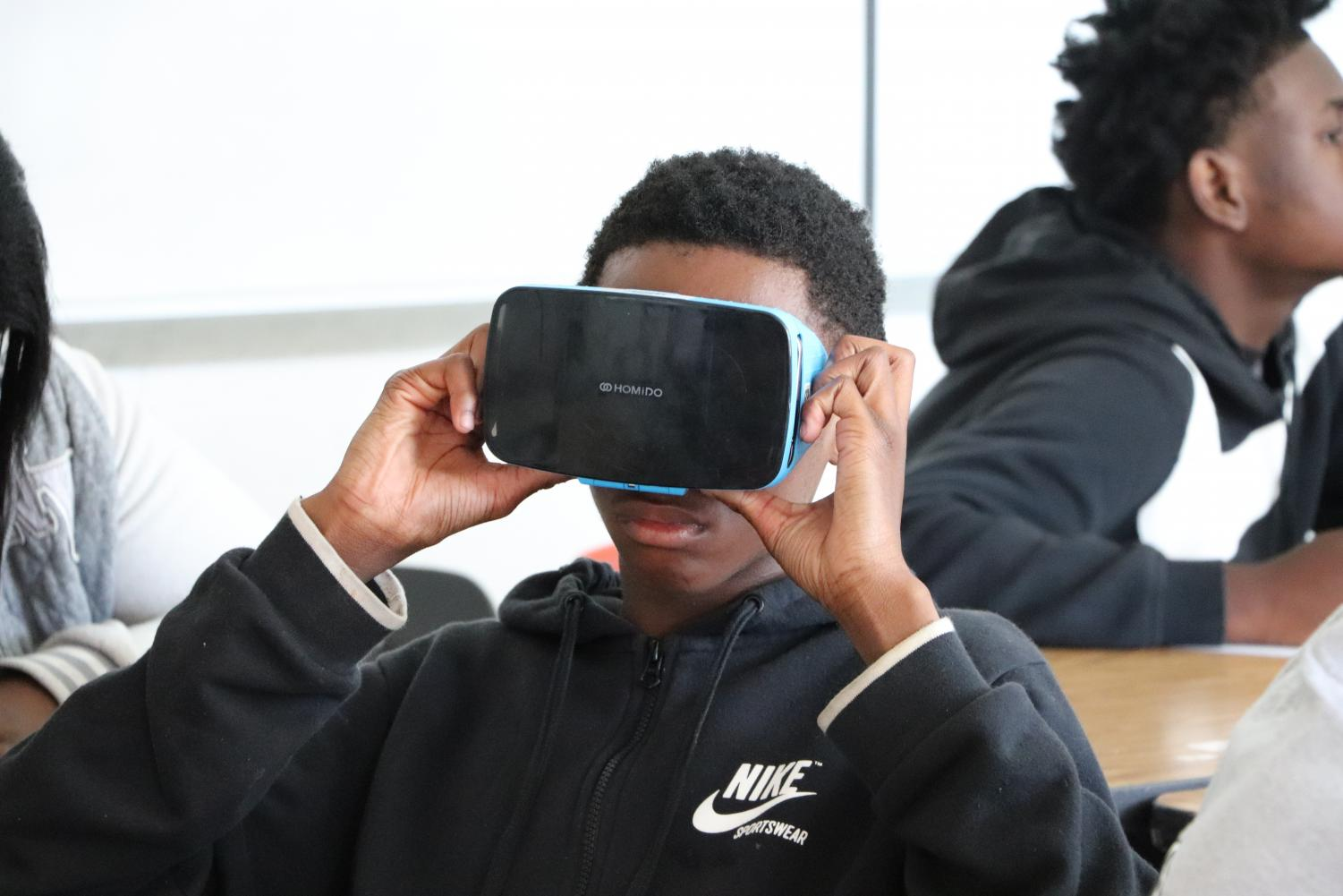 "Getting his first look at virtual reality, Kaizhon Carter, 9,  looks at the characteristics of the tundra ecosystem and fills in his worksheet with the detail he sees. For their first virtual reality lab, students viewed examples of ecosystems from across the world, using the goggles purchased by the school through a grant from Gear Up. ""We affect the environment and the Earth everyday. We are science experiments ourselves,"" Science Teacher Brooke Klett said."