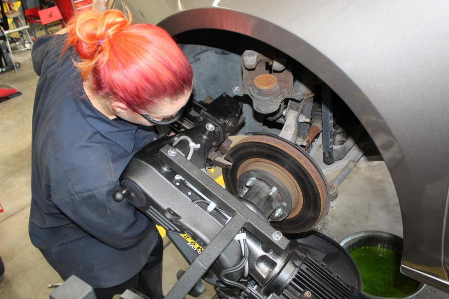 """Positioning the cutting bit, Xena Scott, 12, cuts routers with the on-the-car brake lathe. It was important to be careful with the calibration and to be precise for the best results. """"Without precision, the brakes wouldn't be very smooth, which would affect how the car rides,"""" Scott said."""