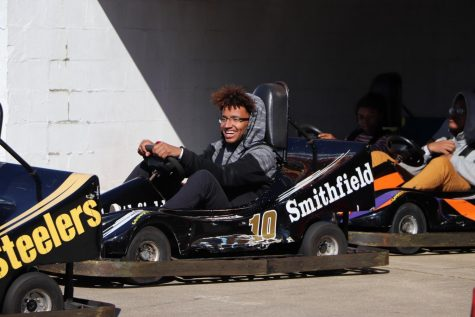 """Ready to race, Senior Tyson Claytor smiles as he awaits the beginning of the kart race against the other band members. The band students went to Motor World in Virginia Beach the day after their competition at Kecoughtan High School in Hampton to enjoy time together before heading home. """"The whole trip there was full of fun and laughter. I really want to go back with my bandmates,"""" Claytor said."""