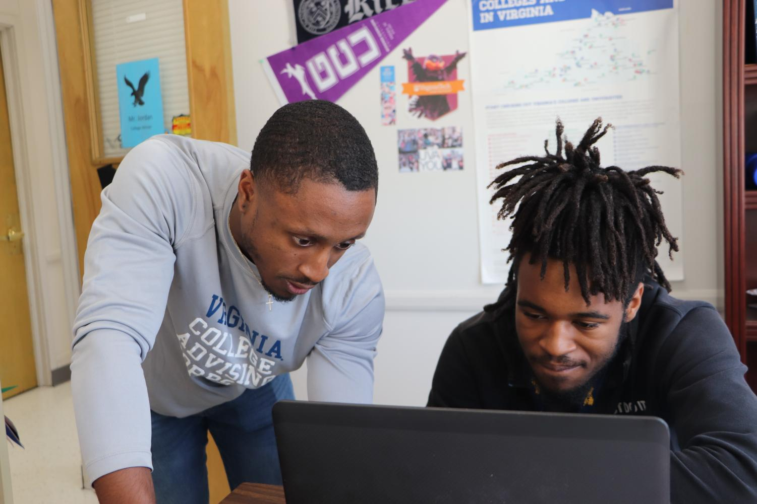 """Helping him register to take the December SAT, College Adviser Kendall Jordan assists Senior Rahmel Goode to create a login and choose the schools that should receive his scored. Jordan said his office doors are open to students in need of assistance in your journey to being college ready. """"I have had at least one one-on-one interaction with 45 percent of the Class of 2020 so far,"""
