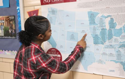 """Senior Taylor Hill visits the map of four-year colleges and universities that accept the Common Application outside of the library. Members of the school counseling and college advising staff organized the information for quick reference, giving students more details about entrance exam dates, application deadlines, and newly released scholarships. """"I haven't received any acceptances at this moment, but the Common Application is the hardest part of applying to college because it's just too much,"""" Hill said."""