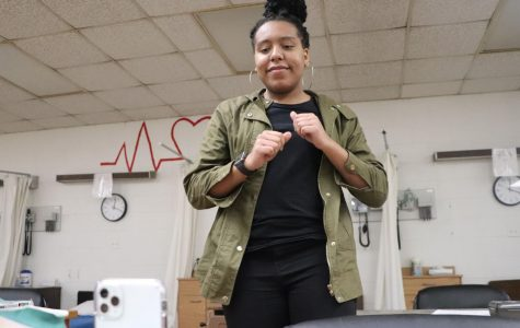 """Focusing on her moves, Junior Amonie Blackwell records herself doing a TikTok dance on her phone during her lunch. Blackwell said she decided to download the app because she wanted to join the hype that was circulated around it. """"I love using TikTok because it's fun. I also love the challenge of learning a new trend, such as the Renegade dance,"""" Blackwell said."""